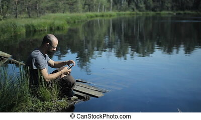 A man sits on a pier of the lake and is video calling on the phone. The beautiful blue lake and forest on background