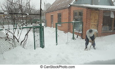 Man with snow shovel cleans street - Eldery man remove snow...