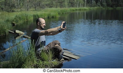 A man sits on a pier of the lake and is video calling on the tablet. The beautiful blue lake and forest on background