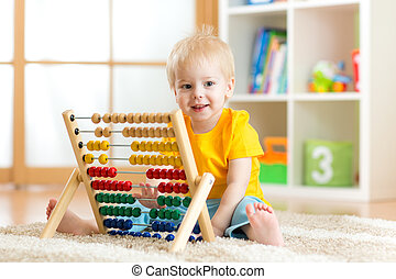 child boy playing with counter toy at home