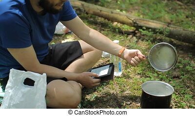 Man reads an e-book in the forest. Near the tourist pot on a gas burner