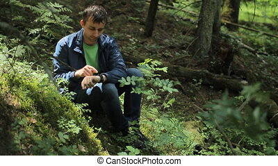 The man in the forest touc smartwatch. It sits on a small cliff green