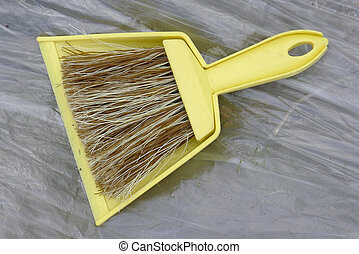 yellow dustpan and brush on a plastic