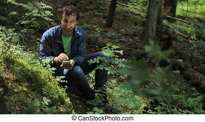 The man in the forest photographed on the phone. It sits on a small cliff green