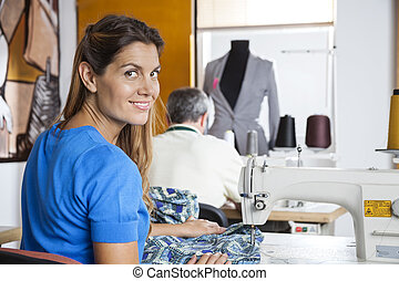 Portrait Of Smiling Tailor Using Sewing Machine - Rear view...