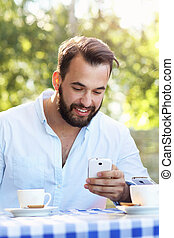 Man with smartphone in restaurant