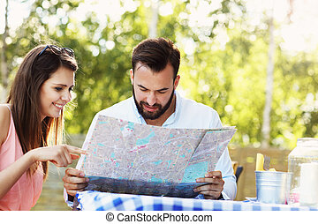 Young couple with map in cafe