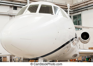 Small private corporate jet in a hangar