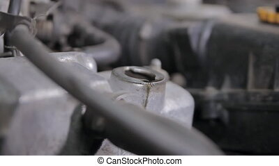 Oil change in a car - A motor cover of an old car is being...