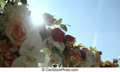 Arch is decorated with fresh flowers and cloth.
