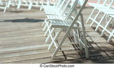 White chairs on a wooden platform in the open air - White...