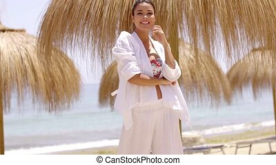 Smiling young woman in bright beach clothes - Smiling...