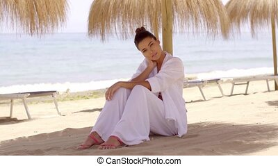 Relaxed woman under shade umbrella at beach - Single cute...