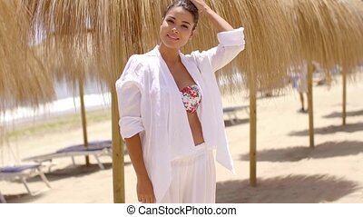 Excited young woman near palapa umbrellas on beach - Smiling...