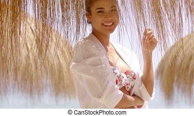 Dancing woman in bikini under palapa umbrella - Happy...