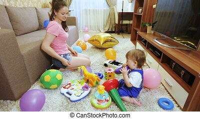 Child with his mother at home with toys - Sitting on floor...