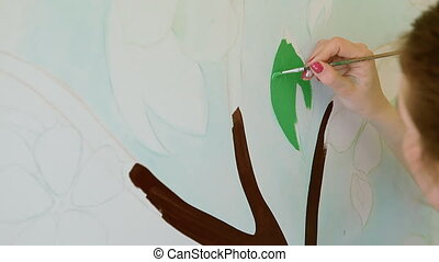 A female artist is painting on the wall in the apartment - A...