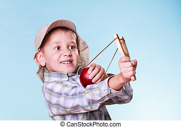 Young boy use sling shot shoot apple - Nature and free time...