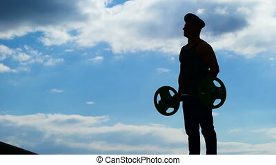A military officer in a beret performs exercises with a barbell.