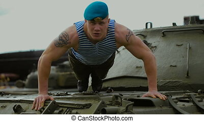 A soldier in a blue beret doing push-ups. He climbed on a...