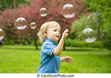 Cute curly baby with soap bubbles children playing, running...