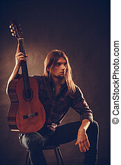 Young man holding guitar - Young stylish man long haired...