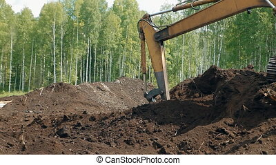An excavator is loading the ground with a bucket - An...