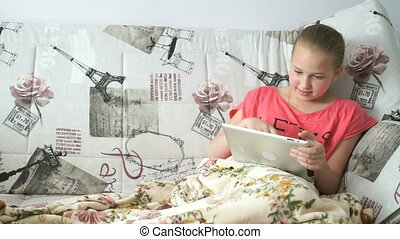 Teenager girl lying on a bed with a digital tablet -...