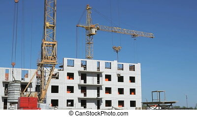 A construction crane delivers cement for builders - The...