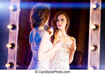 Young beautiful girl in the mirror in a nightclub. Beauty...