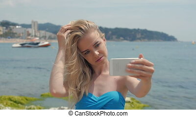 Summer beach vacation girl taking fun mobile selfie photo with smartphone. Cute Asian woman wearing blue sunglasses posing for phone self-portrait photo enjoying suntan in tropical travel holidays.