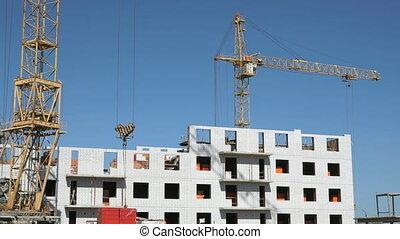 A construction crane delivers the concrete slabs