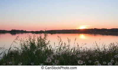 Timelapse of a sunset on the lake in summer - The sun goes...