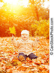 Adult hand holds baby yellow autumn leafs at sunset Kid...