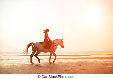 Girl riding a horse on the background of the sea - The image...