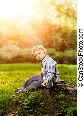 A child at sunset, back light. Kid on the meadow in the park. The baby on the background of the summer. Summer scene