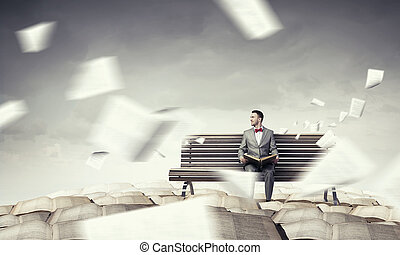 Businessman reading old book Mixed media - Young businessman...
