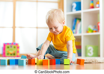 Preschooler child playing with colorful toy blocks. Kid...