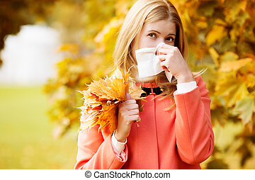 Girl with cold rhinitis on autumn background. Fall flu...