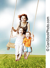 Family fun Mom, daughter, son laughing on a swing against...