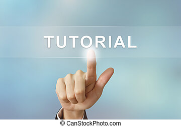 business hand clicking tutorial button on blurred background...