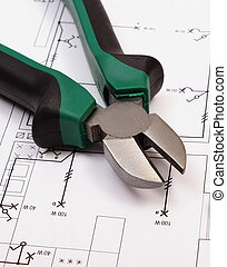 Metal pliers on electrical construction drawing of house