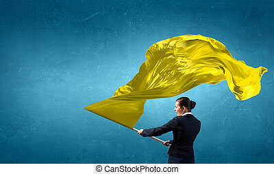 Woman waving yellow flag - Determined businesswoman waving...