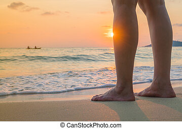 Feet on the sand in sunset time