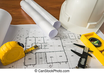 Construction plans with White helmet and drawing tools on...