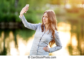 Romantic young girl holding a smartphone digital camera with...