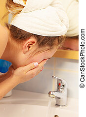 Woman washing face in bathroom Hygiene - Woman cleaning...