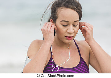 Female runner preparing for outdoor workout on the beach setting