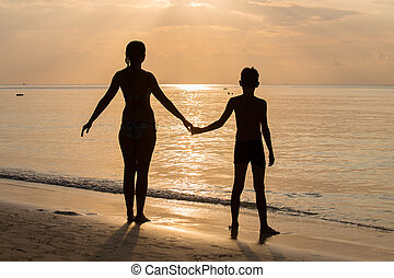 Silhouette mother with her son on the beach during sunset