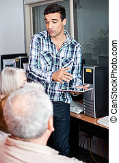 Teacher Holding Digital Tablet While Explaining To Senior...